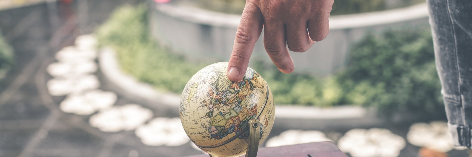 finger pointing to a location on a globe