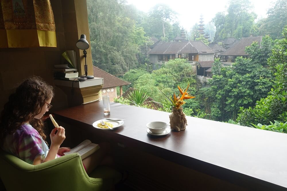 Girl reading at breakfast with beautiful view