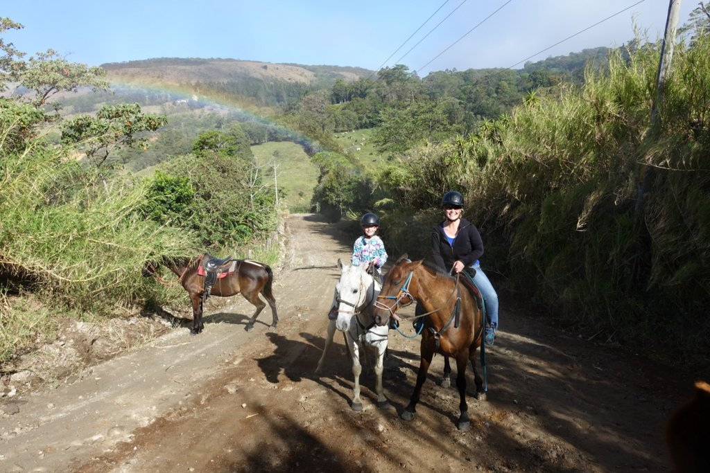 Riding horses with a rainbow in the backround