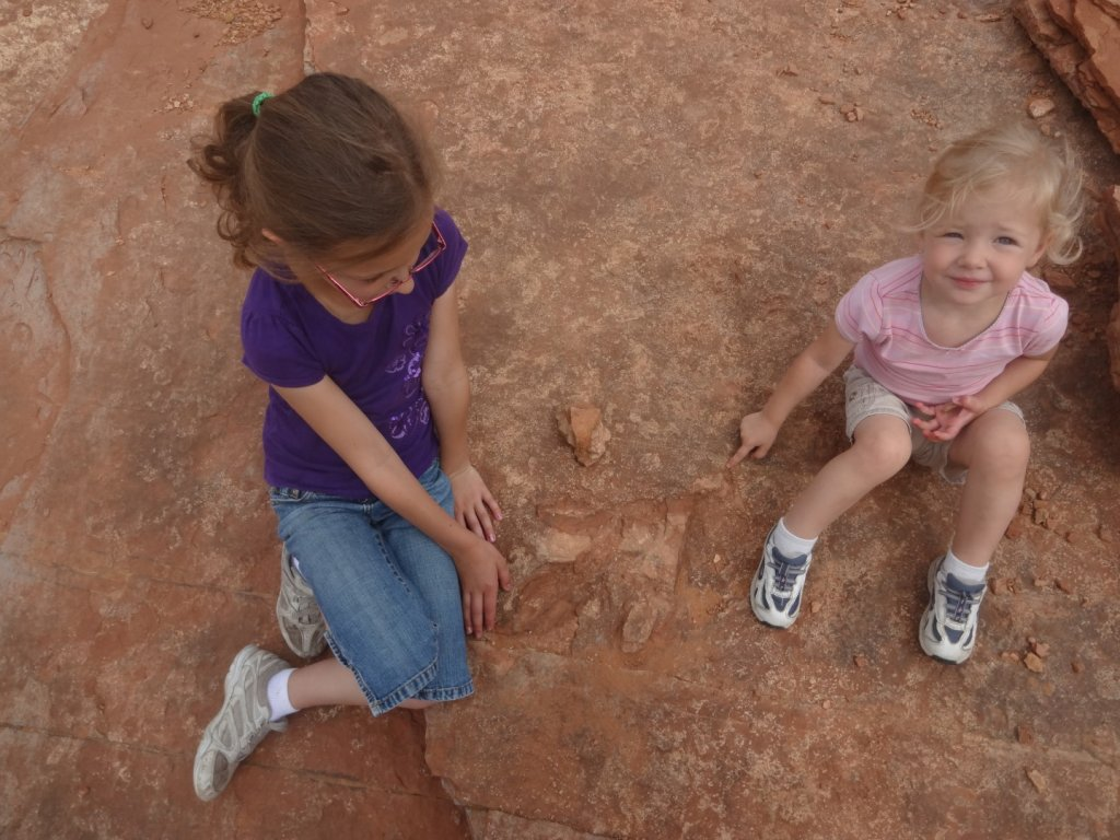 kids sitting by dinosaur track