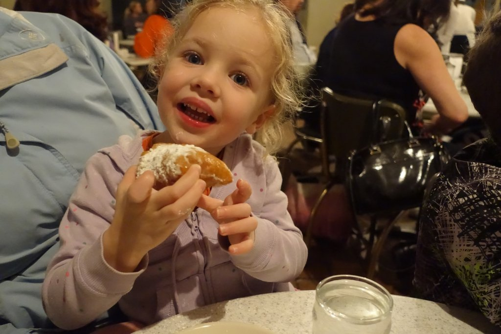 girl eating a beignet