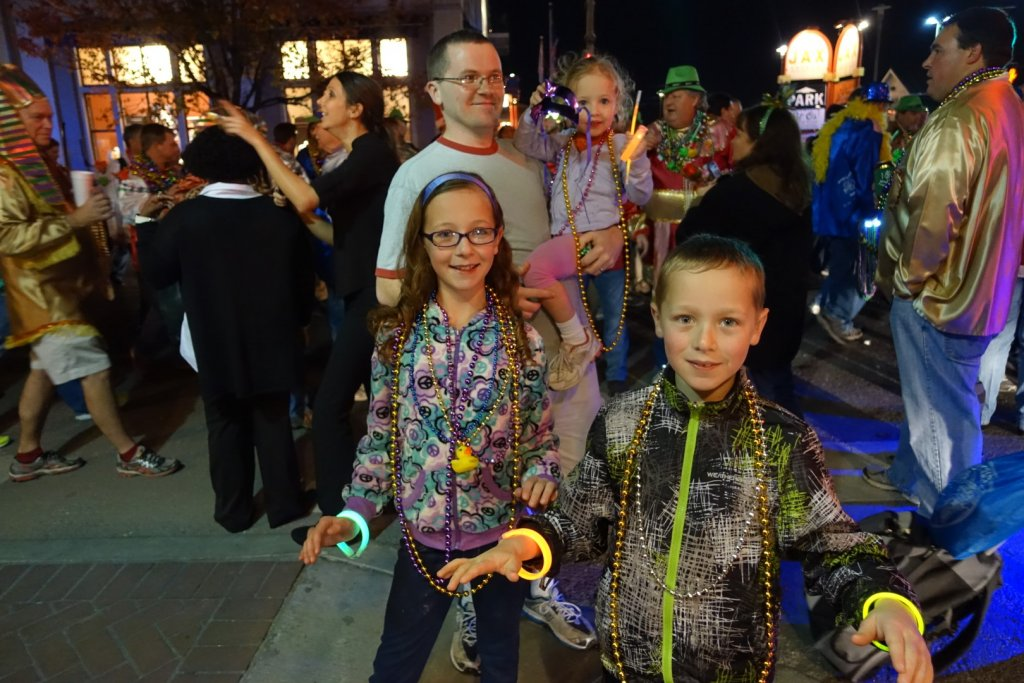 family with necklaces and light up trinkets from parade