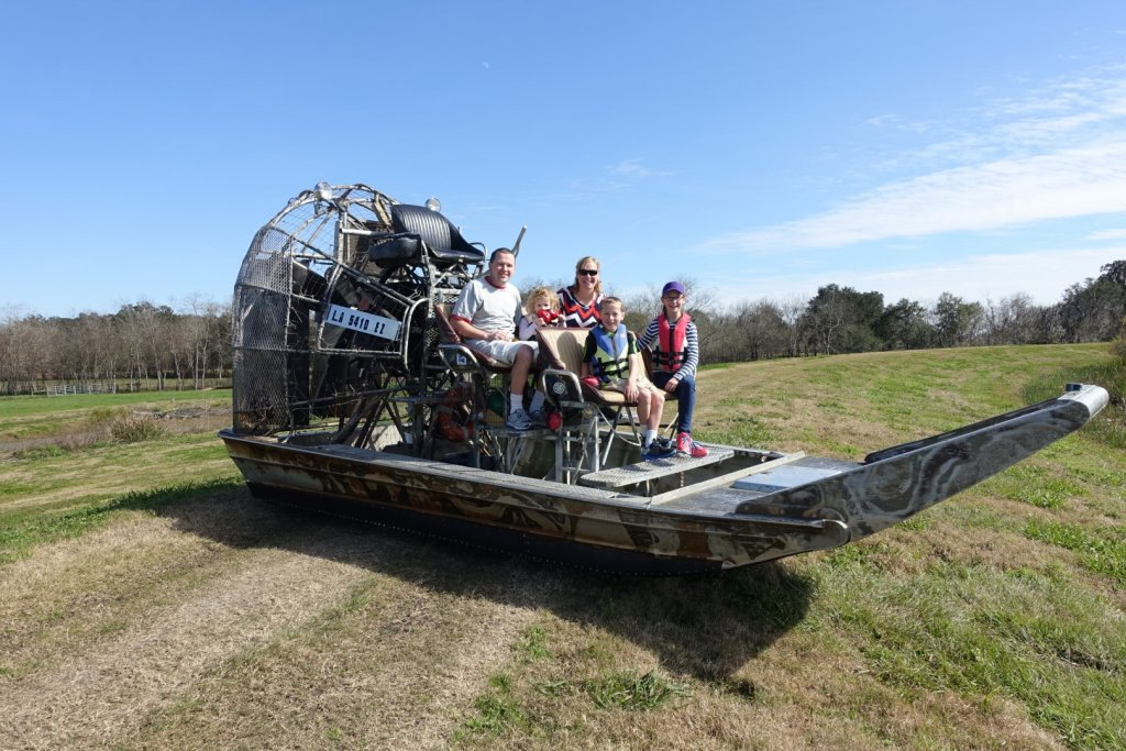 family sitting on an airboat