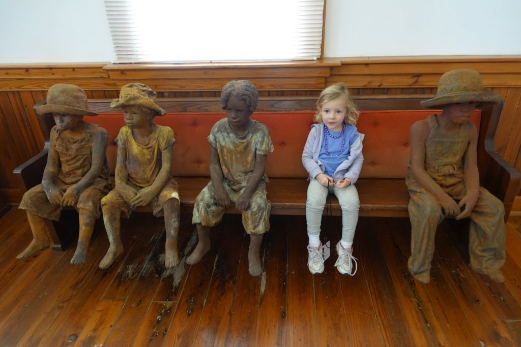 girl sitting with statues of slave children