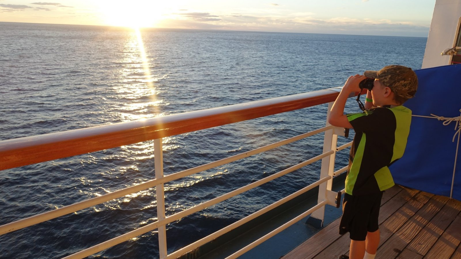 Boy looking into the ocean through binoculars from cruise ship