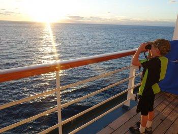 Boy looking into the ocean through binoculars from cruise ship