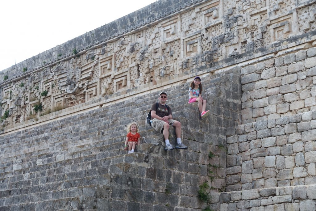 father and daughters sitting on steps of a Mayan temple