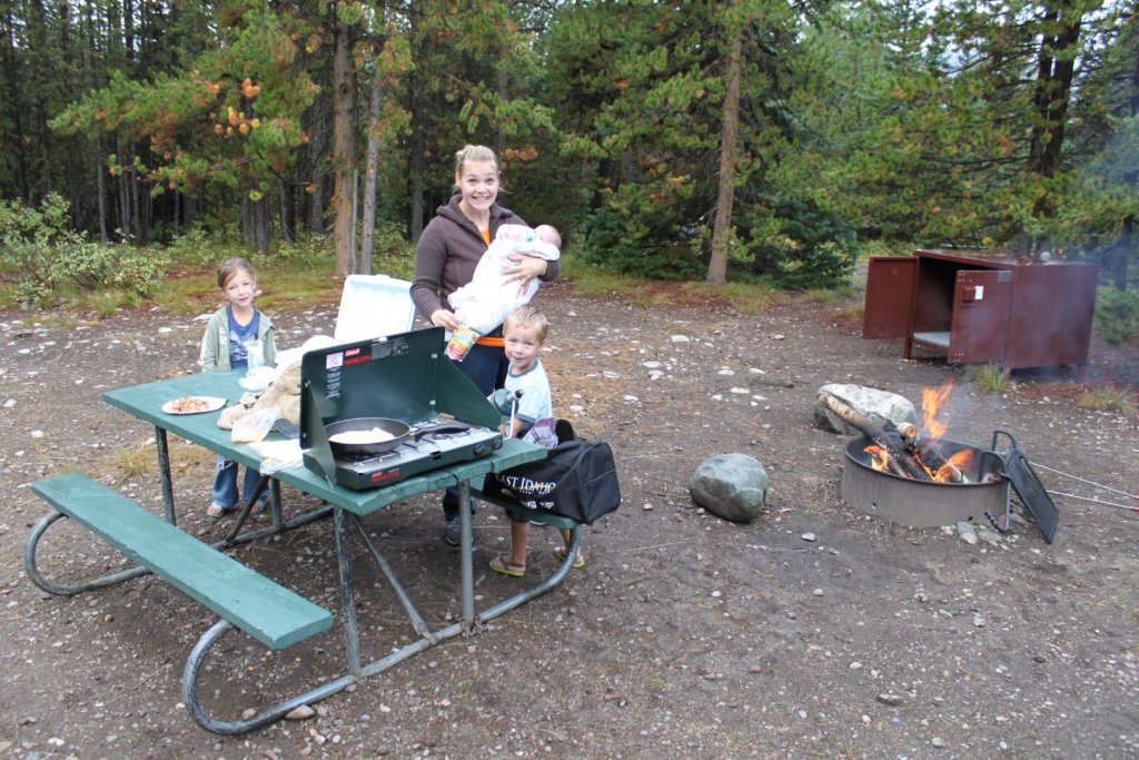 mom and kids with campfire and campstove