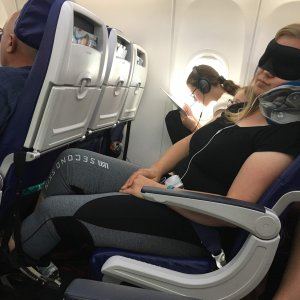 sleeping on an airplane with Trtl pillow, foot hammock, eye ask, headphones