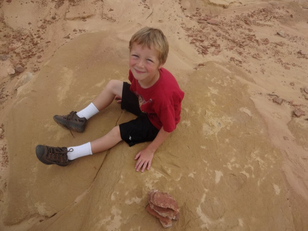 boy with hand next to dinosaur print in rock