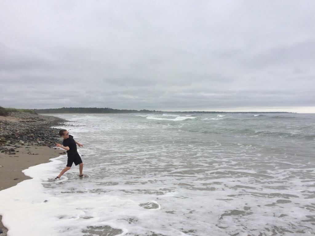 boy throwing rocks into the ocean