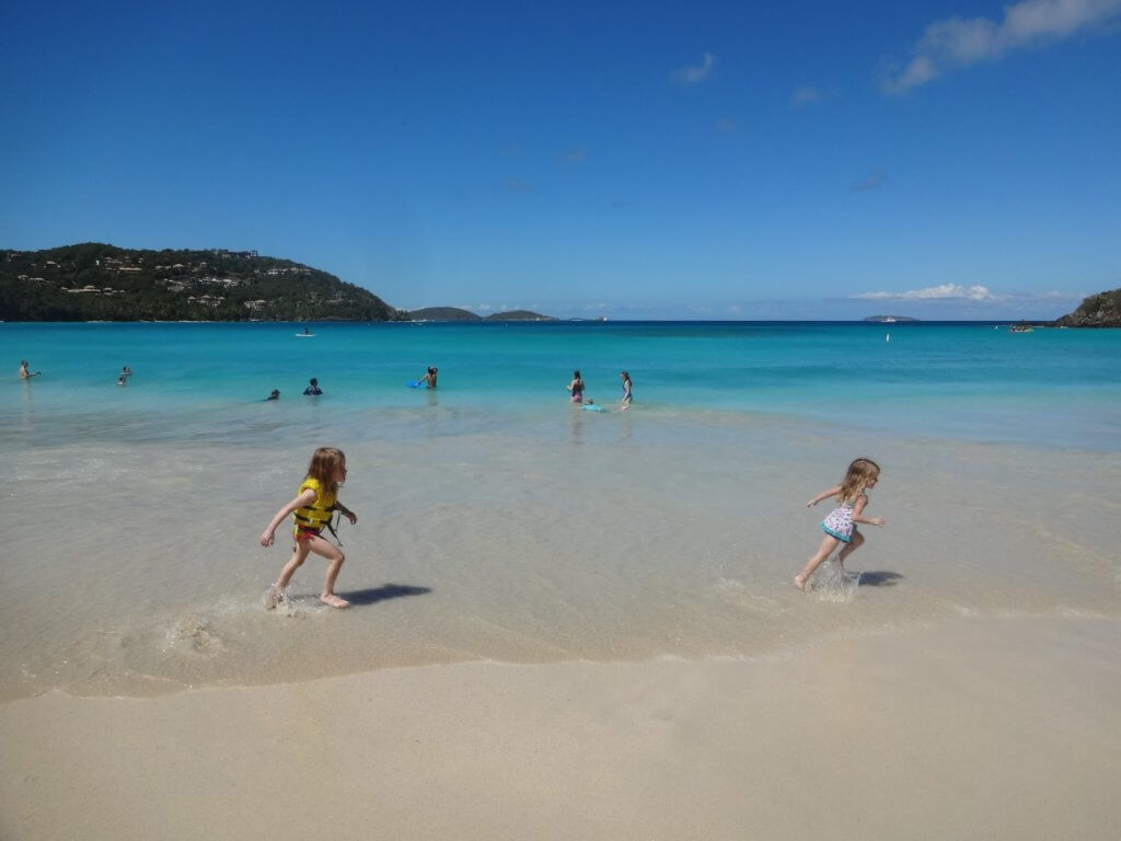two girls running on a beach