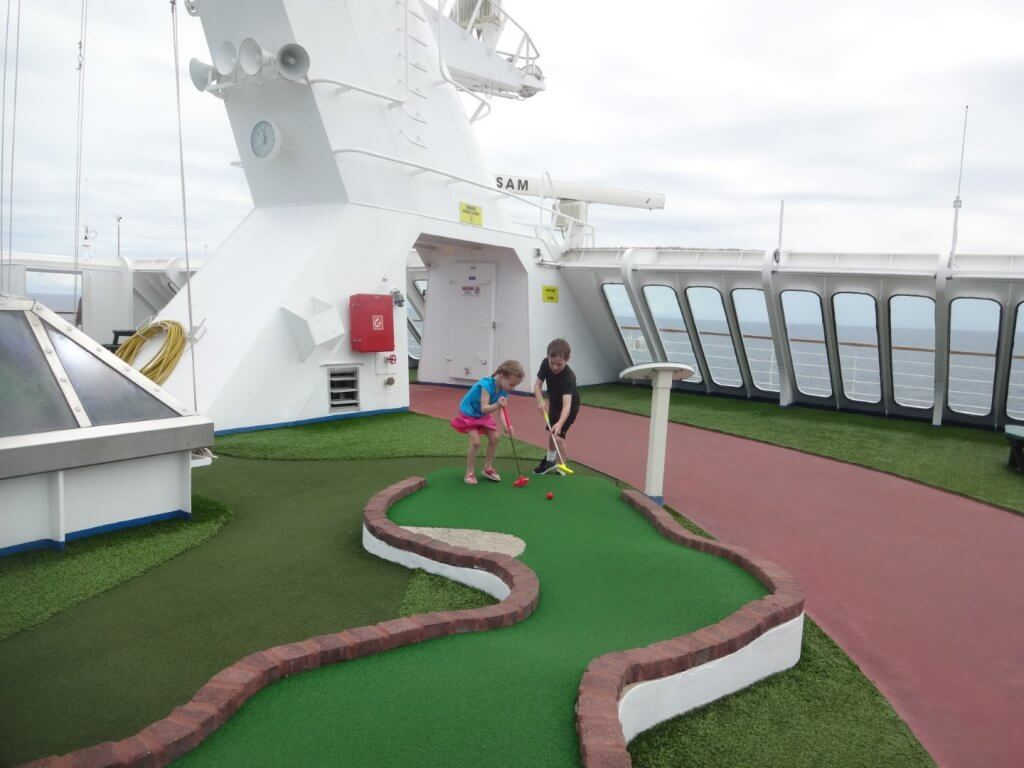 two kids playing mini golf on a cruise ship