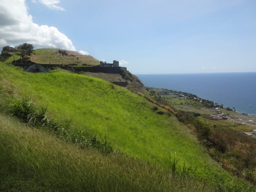 grassy hill with ocean and fortress in the background