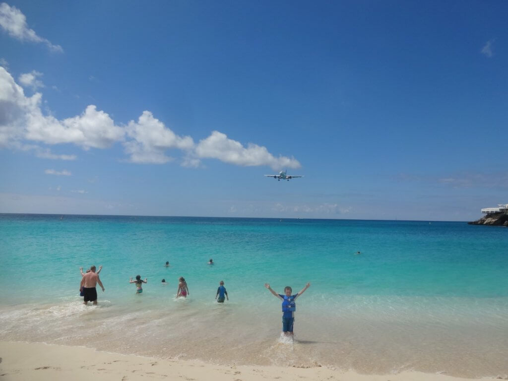 Boy in the ocean with an airplane overhead