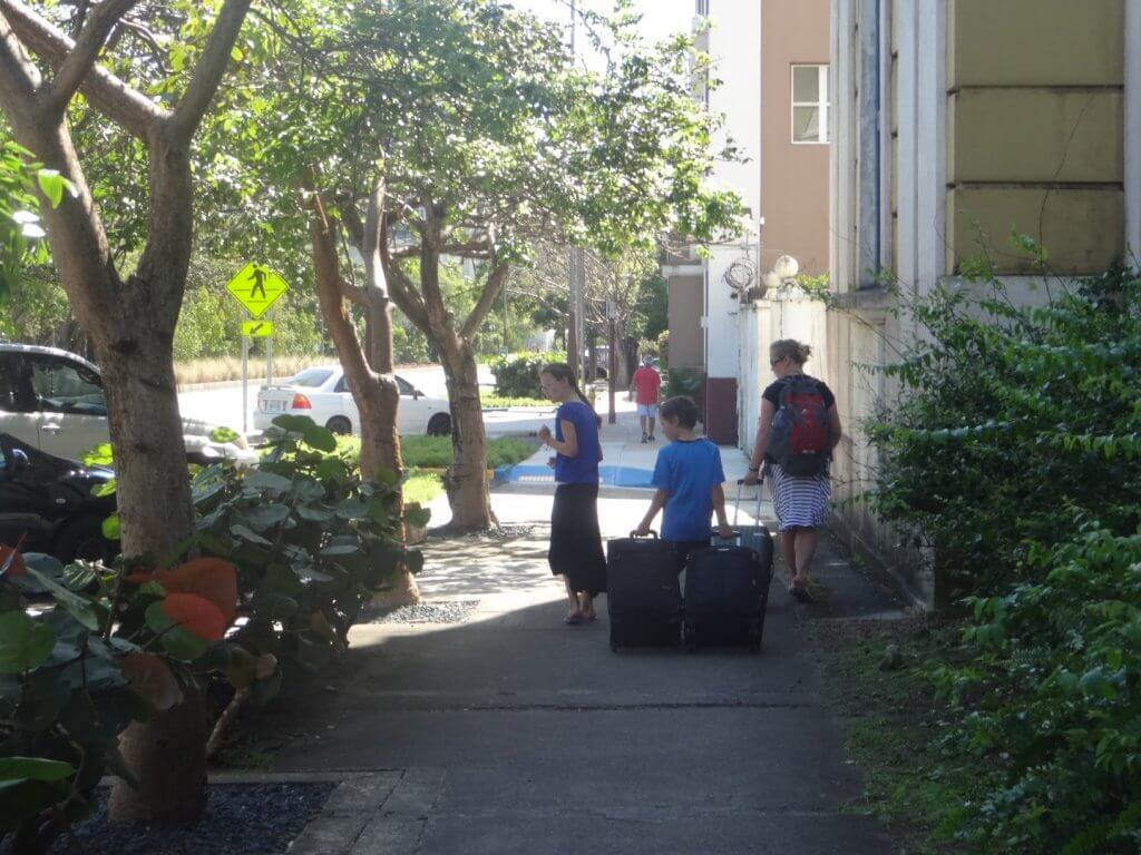 Mom and kids walking on the sidewalk with luggage