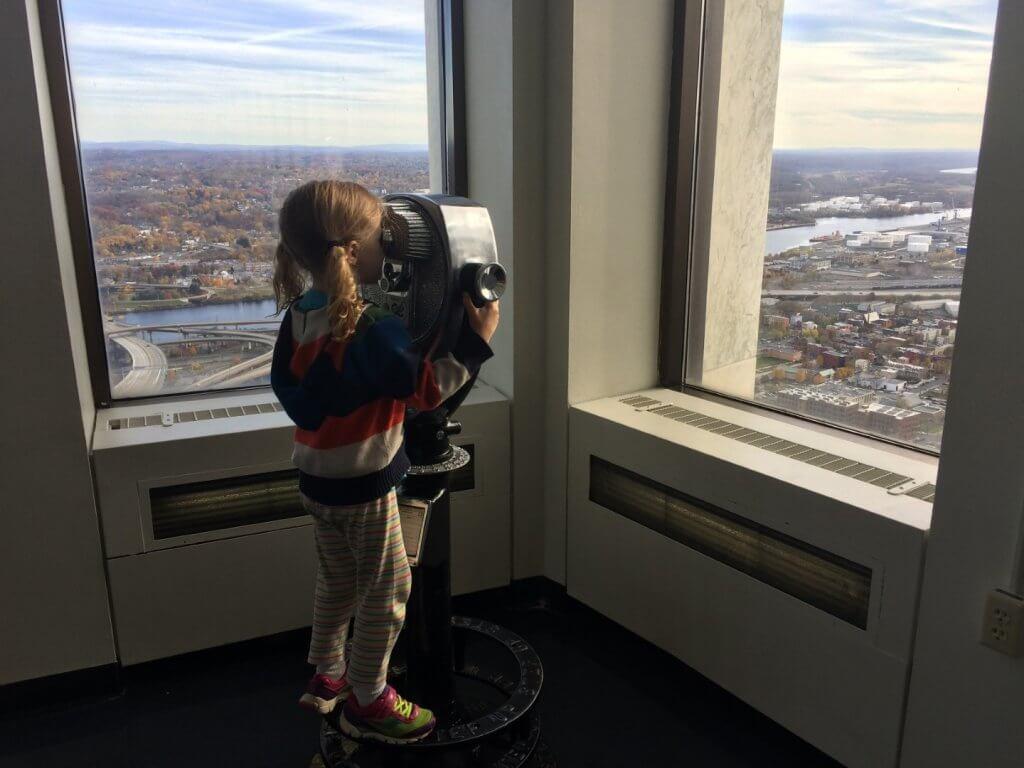 girl looking through binoculars at city through windows