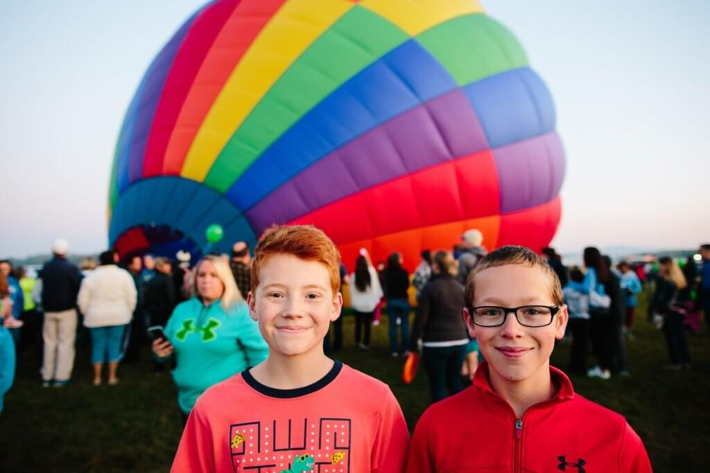 two boys in in front of hot air balloon inflating