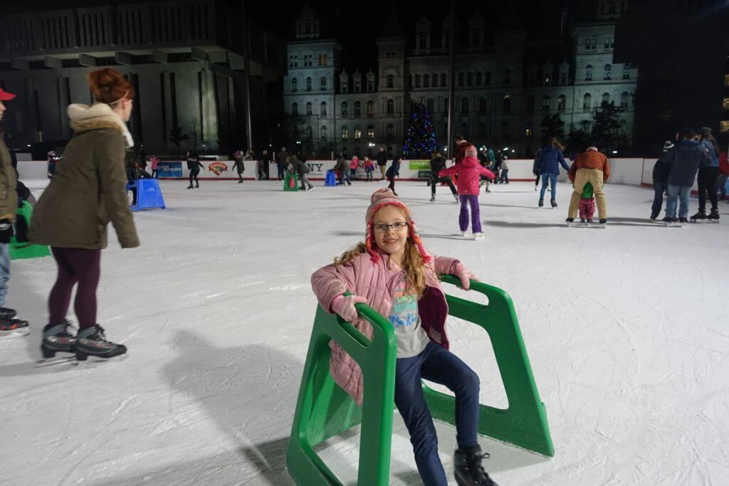 young girl ice skating with skate aid