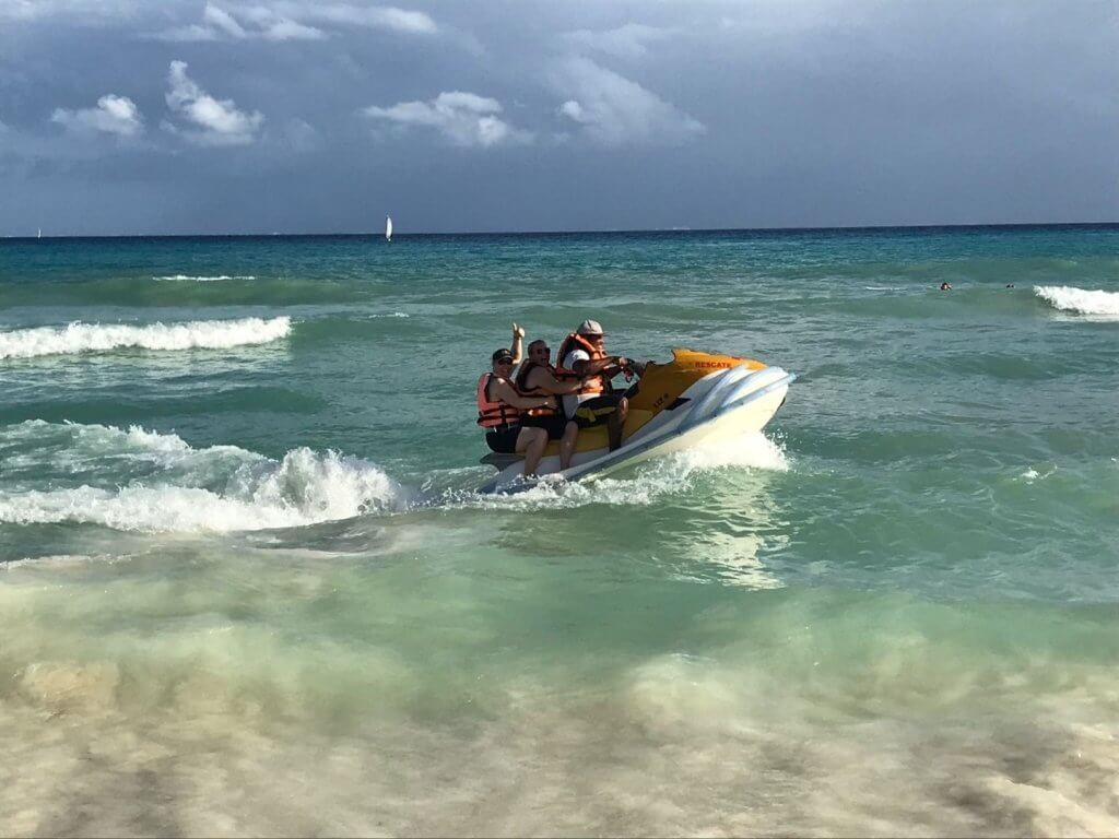 three people on a jet ski in the ocean