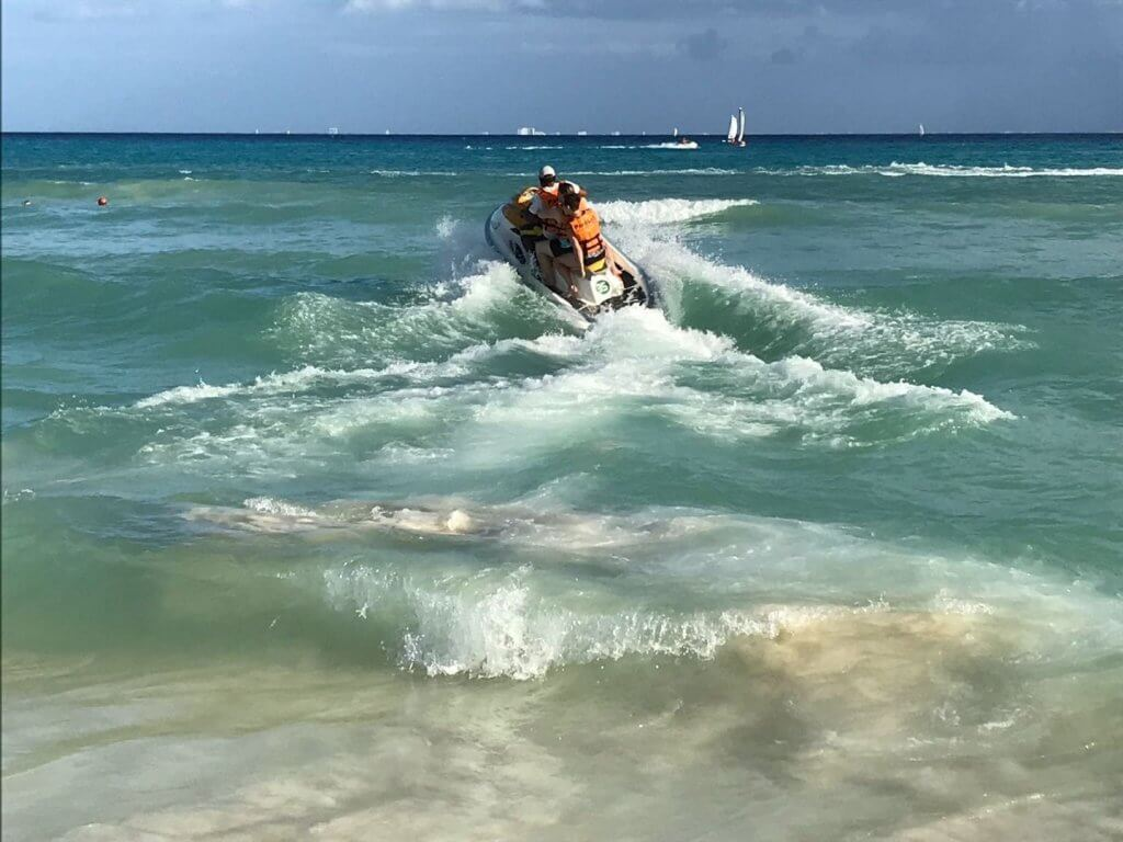three people on a jet ski in the waves