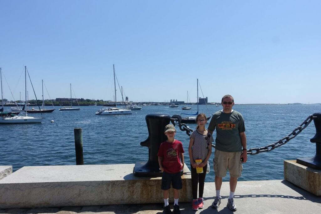man and two kids in front of water