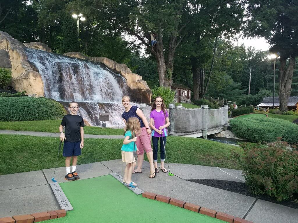 mom and kids playing mini golf with waterfall background