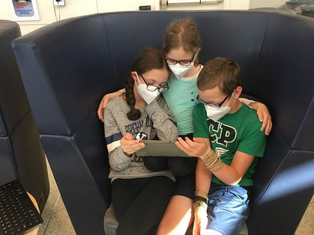 kids wearing masks and watching tablet