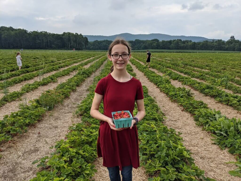 girl holding strawberries in berry patch