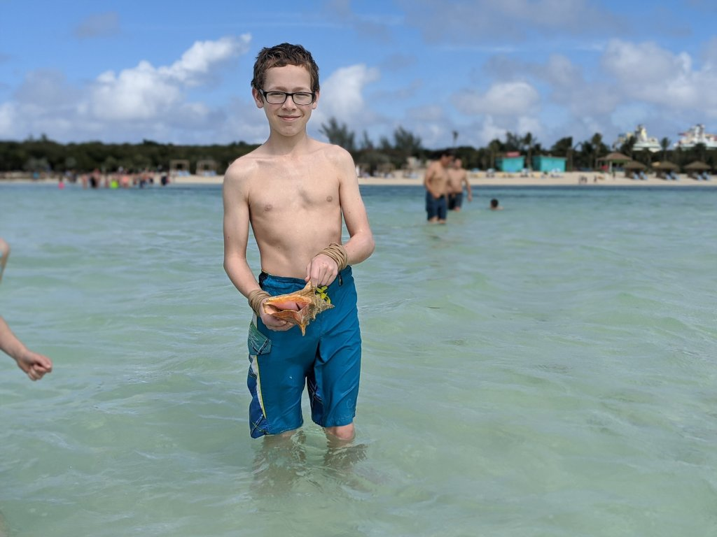 boy with shell in the ocean