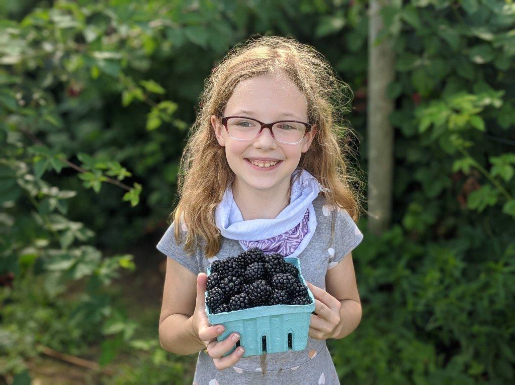 girl holding fresh blackberries