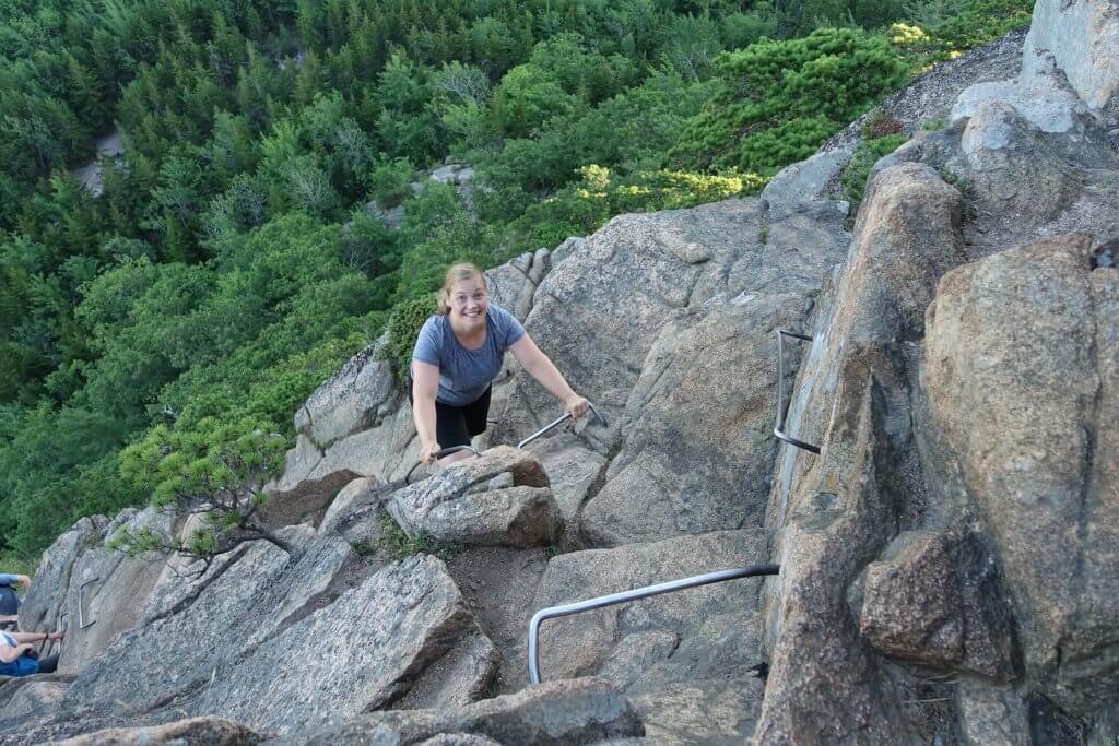 woman climbing metal rungs on mountain