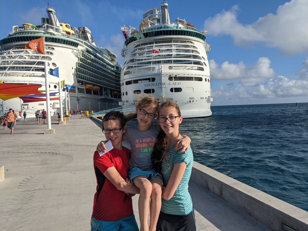 three kids in front of cruise ships