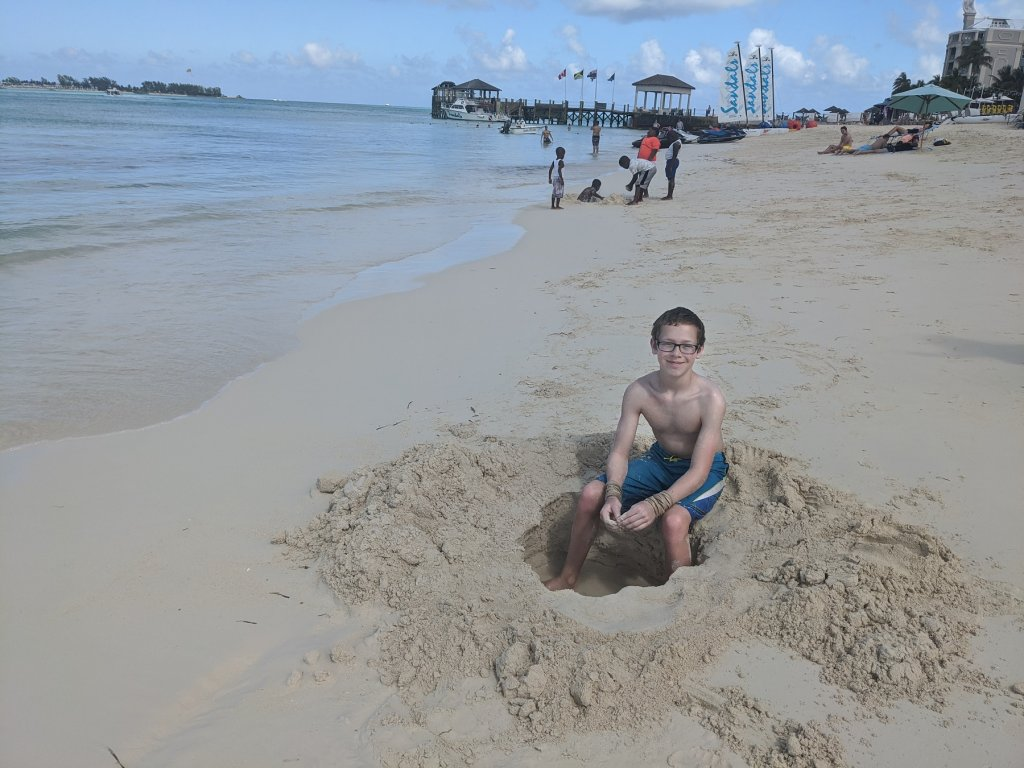 boy sitting on the sand