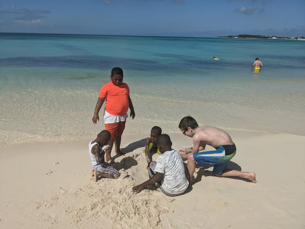 boys digging in the sand on beach