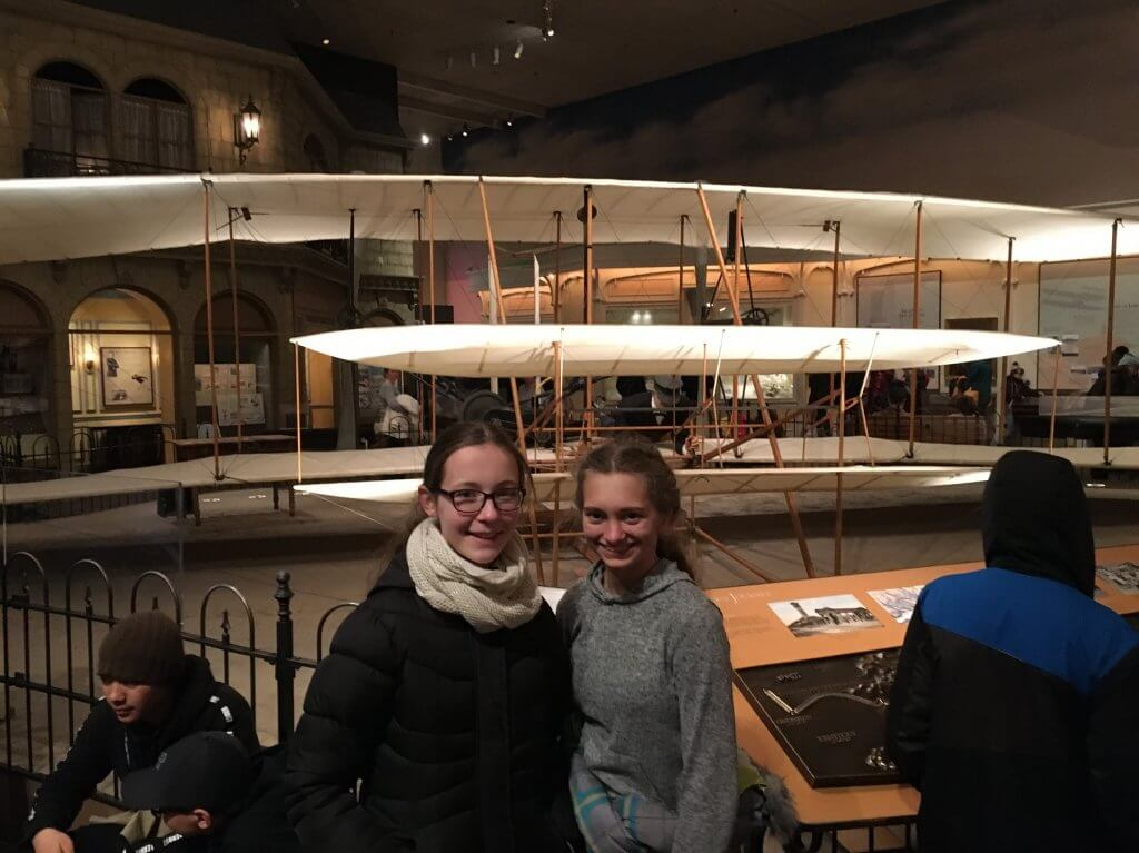girls in front of airplane display at museum