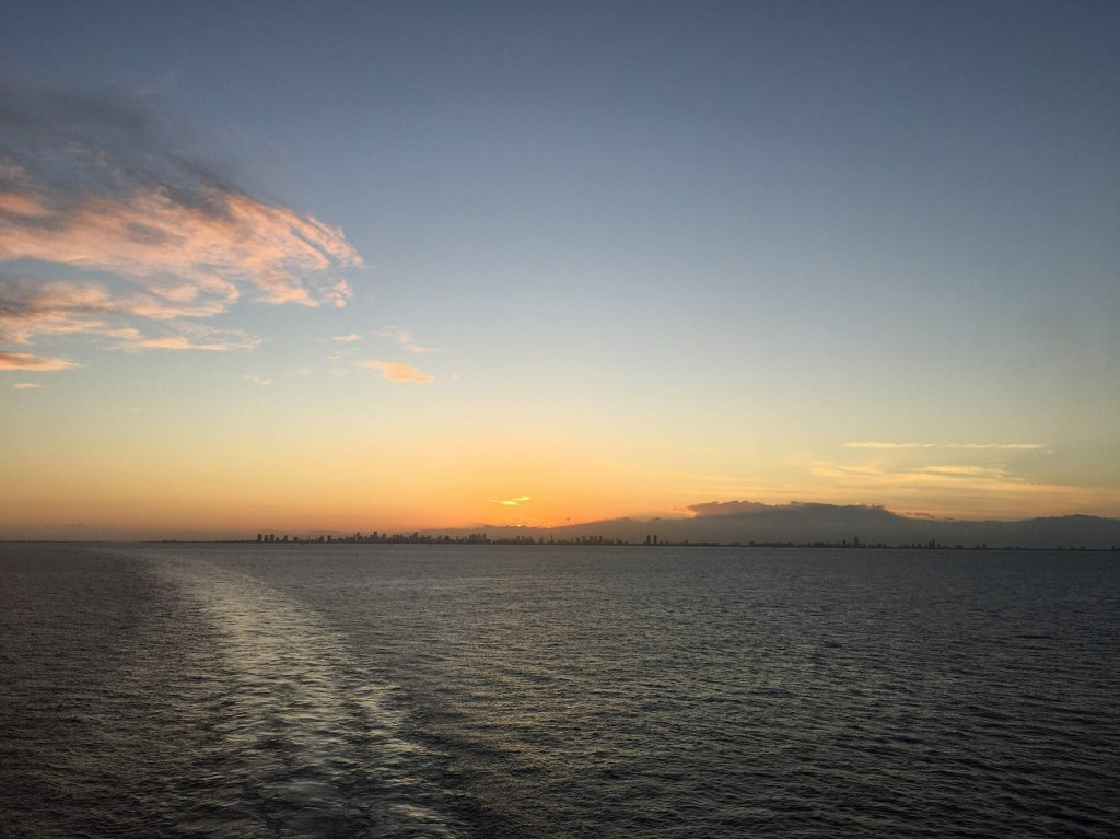 Sunset over city from the ocean