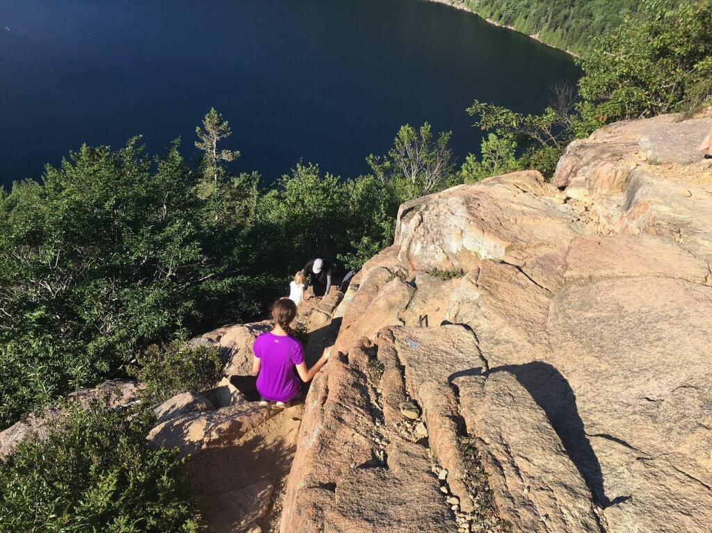 people climbing down rocks