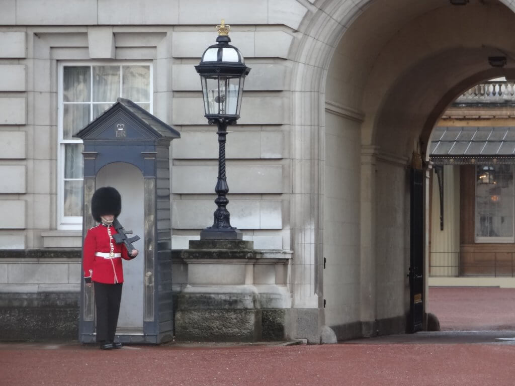 guard wearing red coat and tall black hat