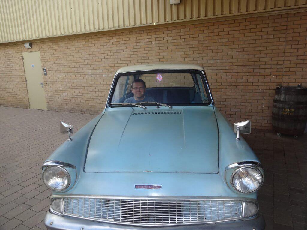 man in a blue car