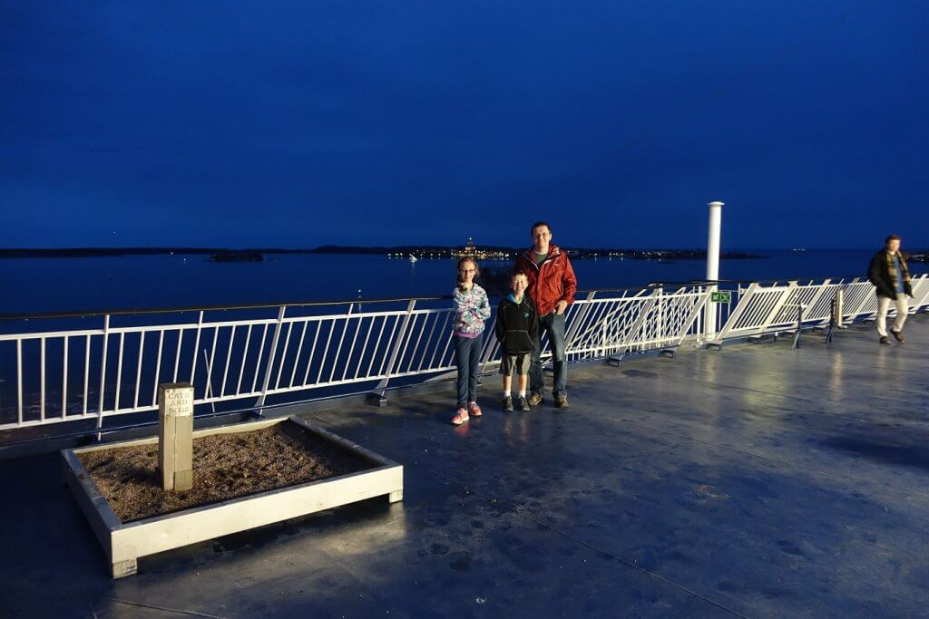 father and kids standing on ferry at night