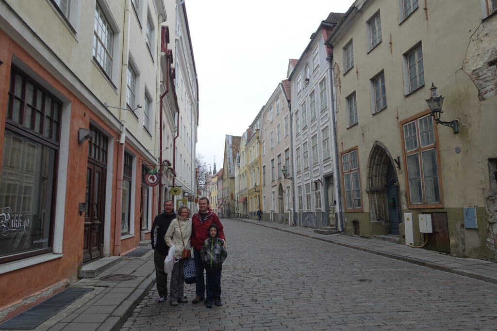 four people standing in street of old town