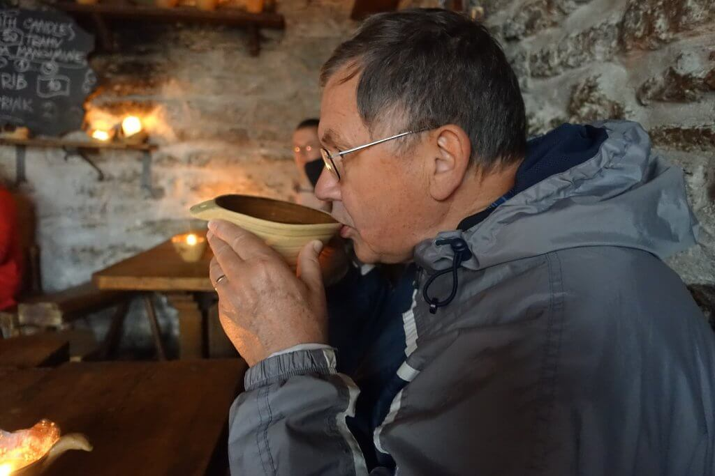 man drinking soup from a bowl