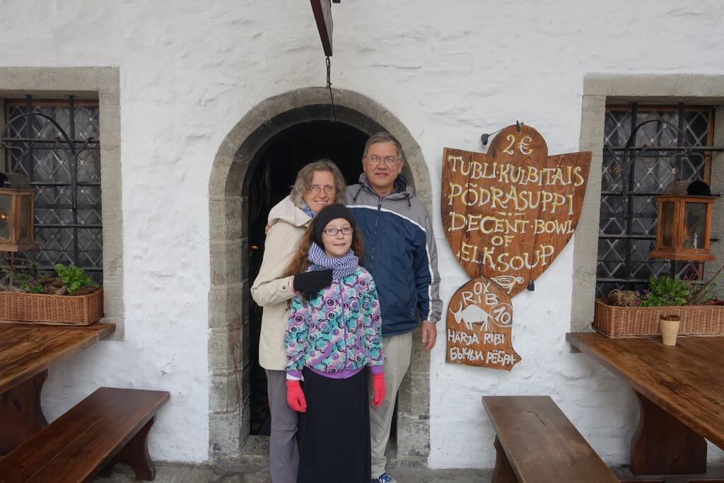 man, woman, and child in front of arched door