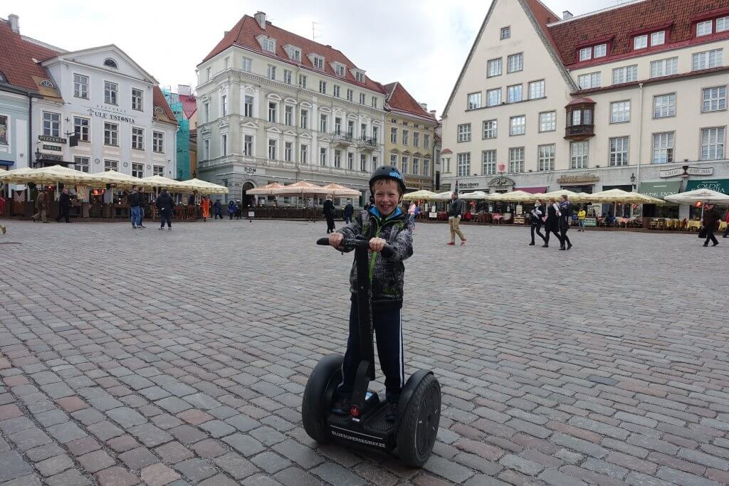 boy riding a Segway on cobble street