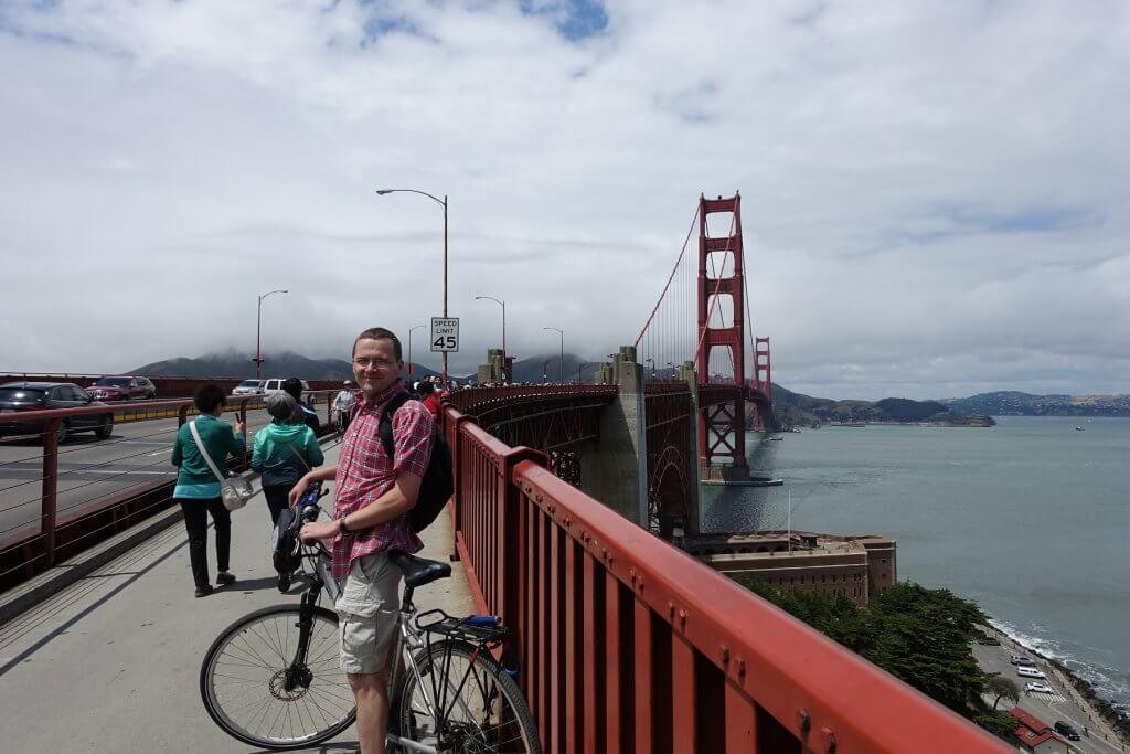 man on bridge with bike