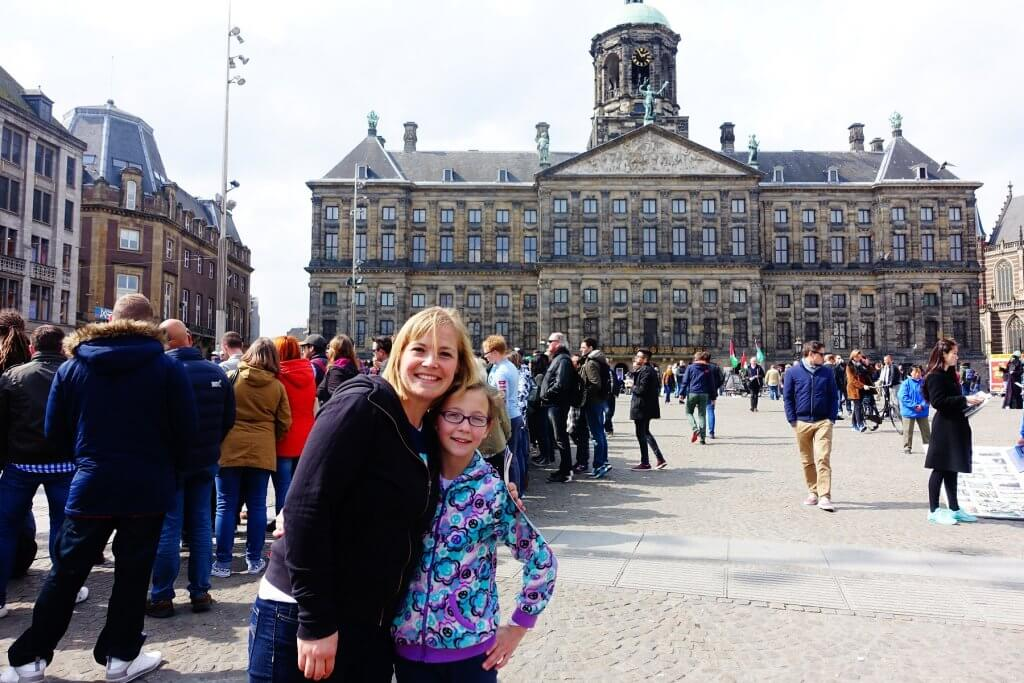 mom and daughter in front of old building