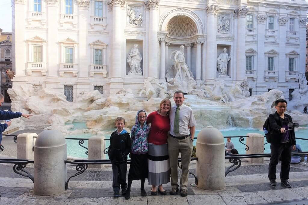 family in front of fountain with sculptures