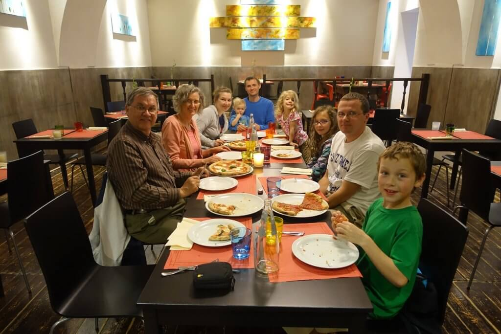 family eating pizza at long table