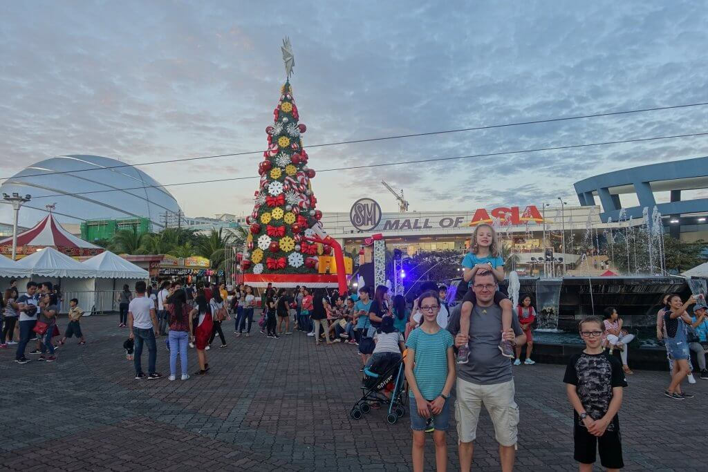 famkiy in front of mall with Christmas tree